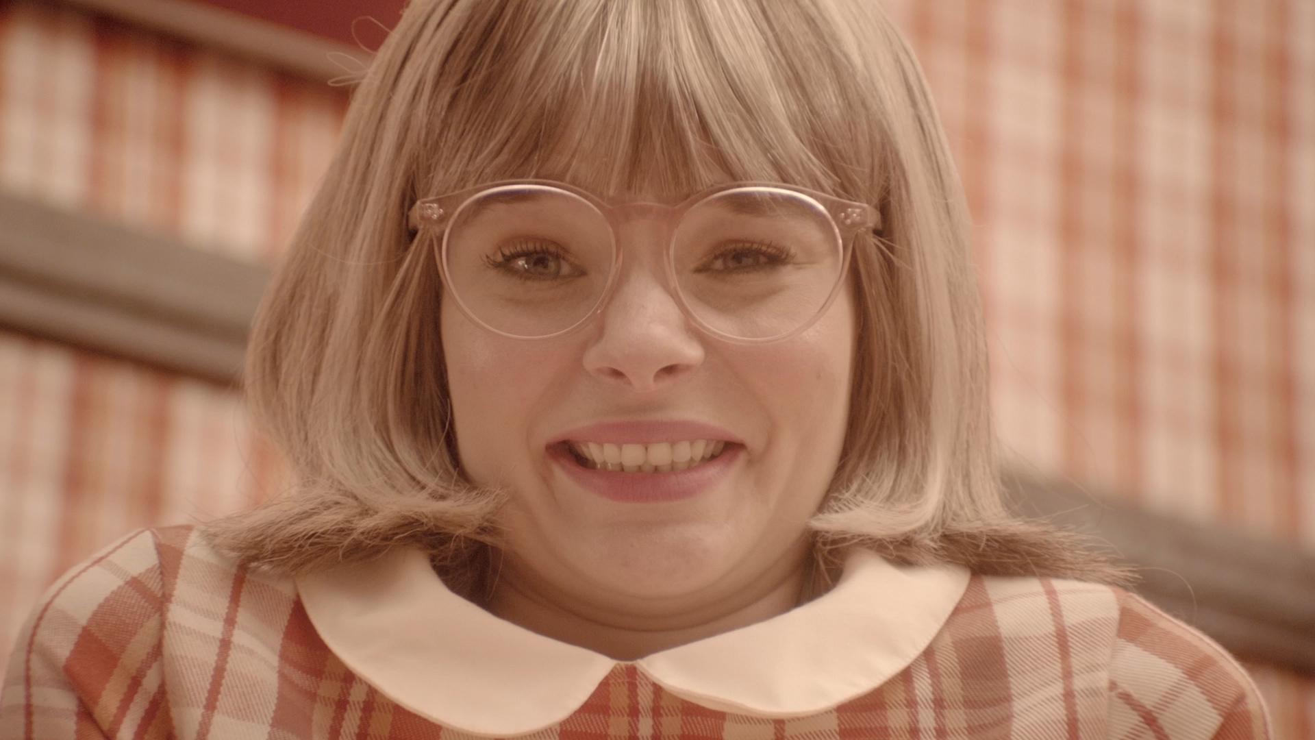 Na imagem, uma atriz adulta interpreta uma criança, com cara de surpresa. A personagem veste roupas xadrês nas cores rosa e branco, usa óculos rosa e tem cabelos loiros. A parede atrás da menina também é xadrês, nas mesmas cores: rosa e branco.