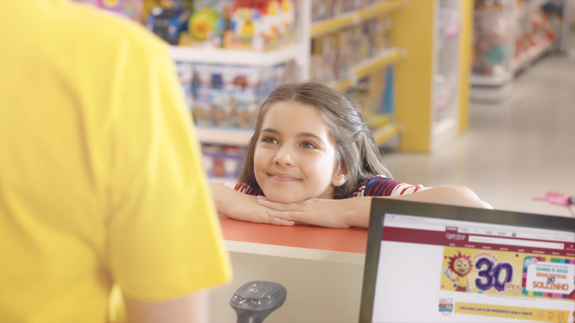 Uma menina apoia a cabeça sobre suas mãos sobre o balcão da loja de brinquedos Ri Happy. Ela olha para o atendente do caixa enquanto sorri.