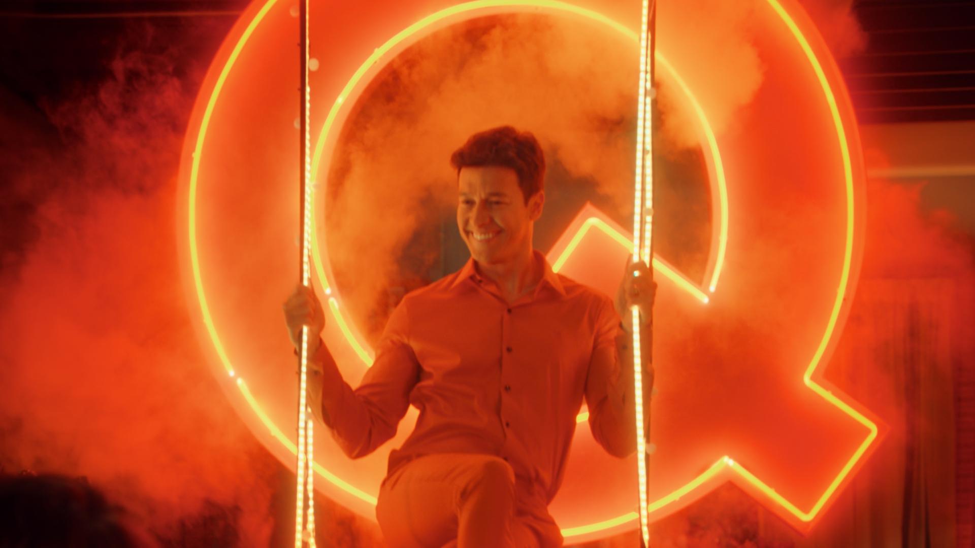 Na imagem, Rodrigo Faro está sentado em um balanço, segurando nas cordas, enquanto sorri. No fundo há fumaça e uma letra Q iluminado por neon.