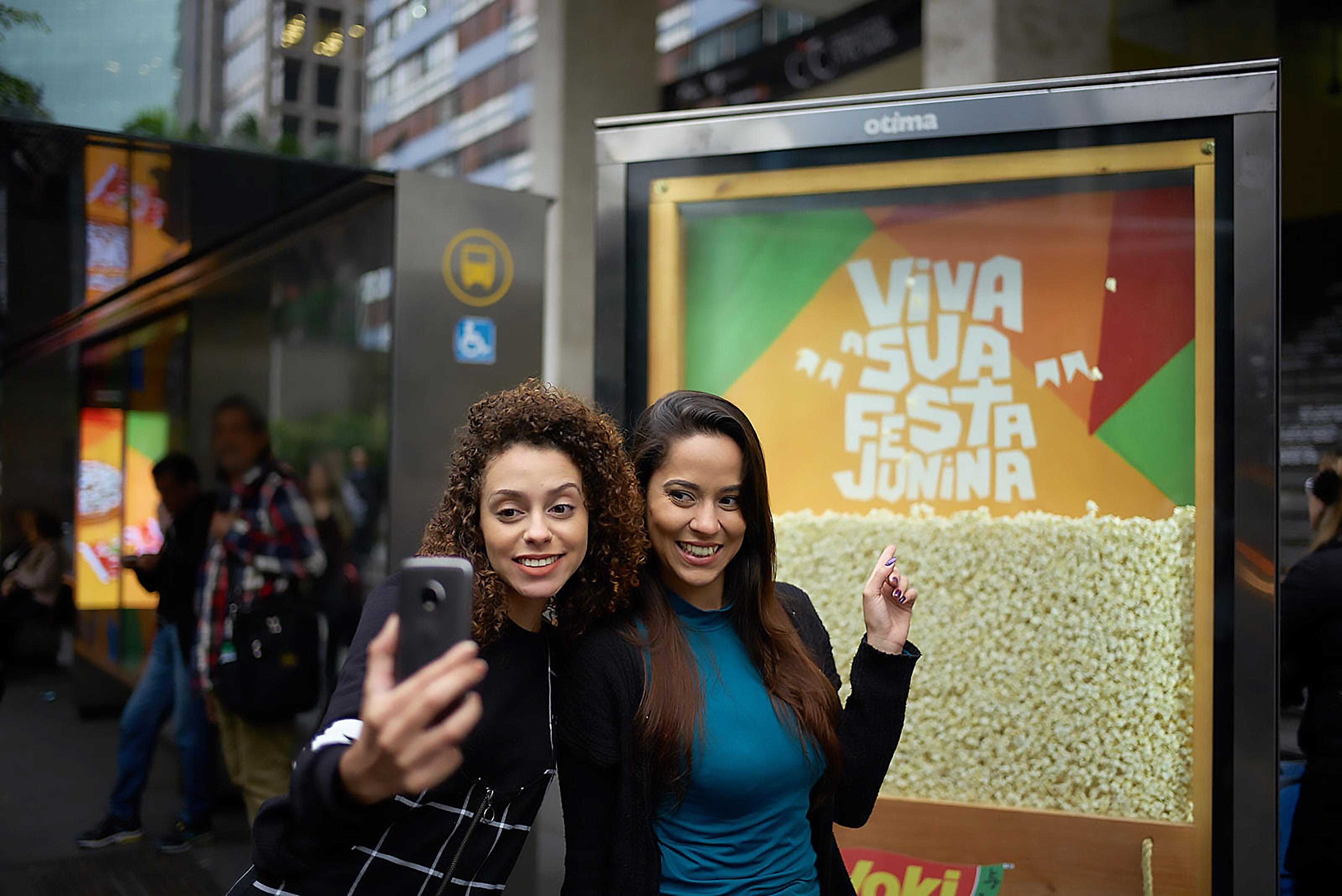 Na imagem, duas mulheres posam para uma selfie em frente ao display publicitário Yoki em um ponto de ônibus. Dentro do display há pipoca pronta com a frase: Viva sua festa junina.