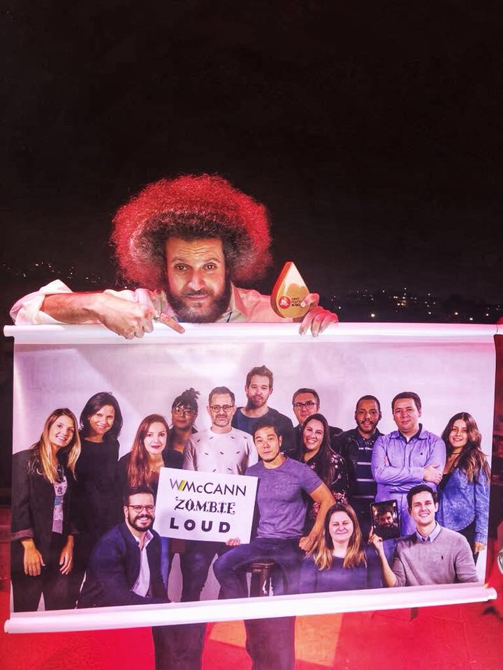 Na imagem, Hugo Rodrigues segura uma foto da equipe da WMcCann