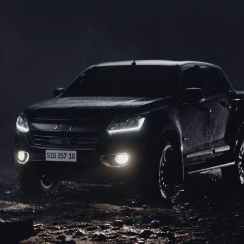 Na imagem, há um Chevrolet S10 Midnight em um ambiente escuro