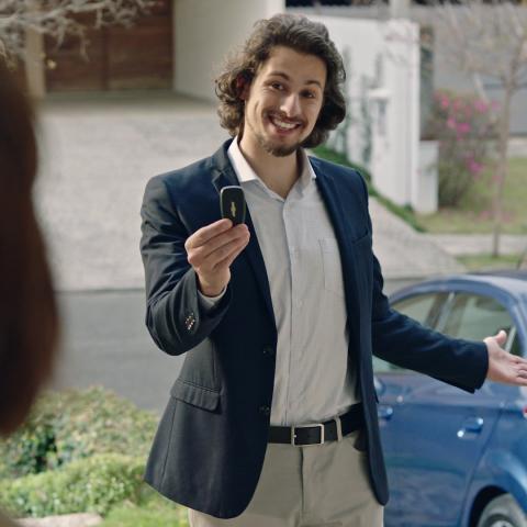 Um rapaz oferece as chaves do carro à seus pais.