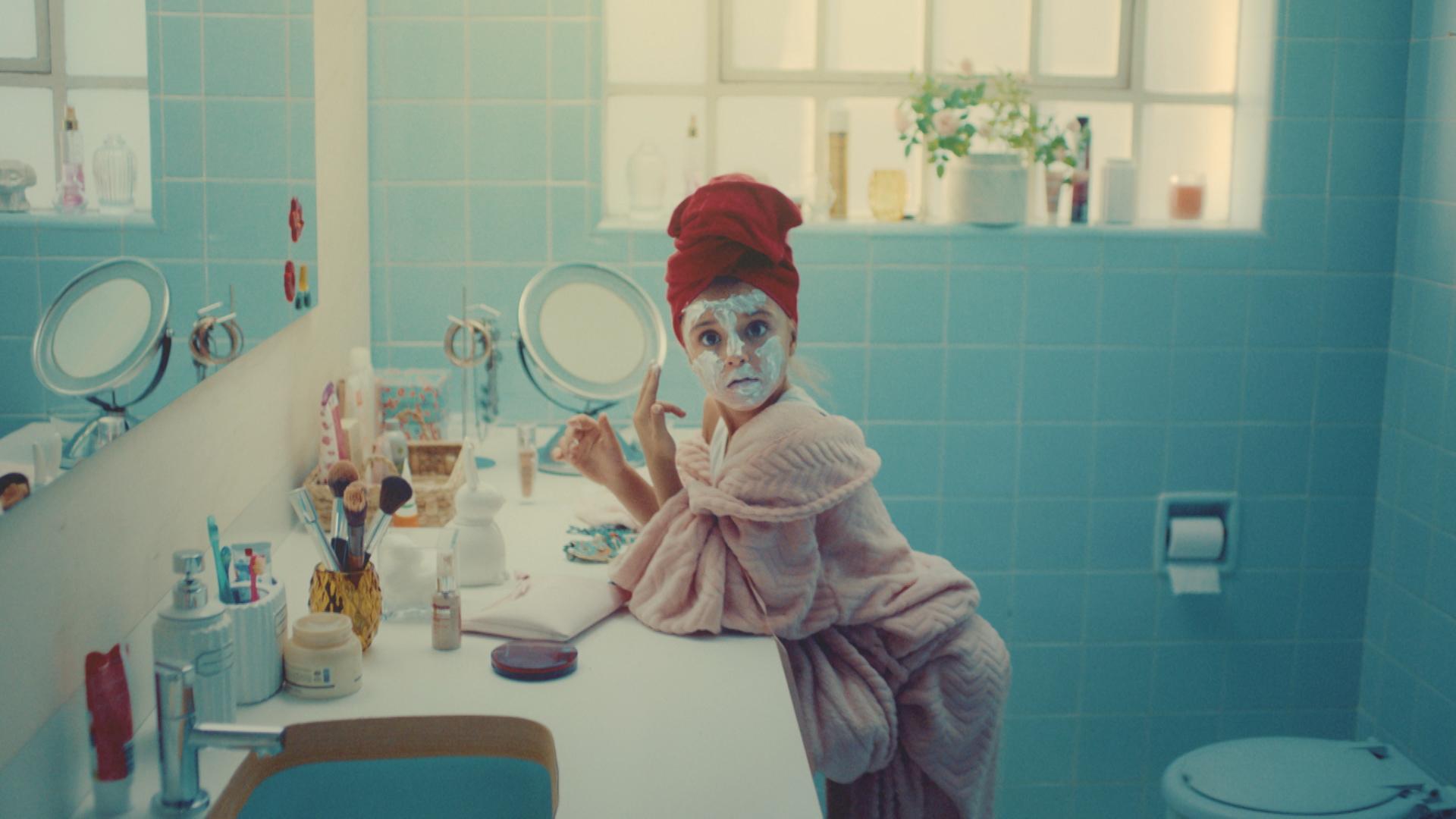 Uma menina faz cara de surpresa quando é pega vestindo roupão de banho e toalha na cabeça enquanto passa uma máscara de beleza no rosto