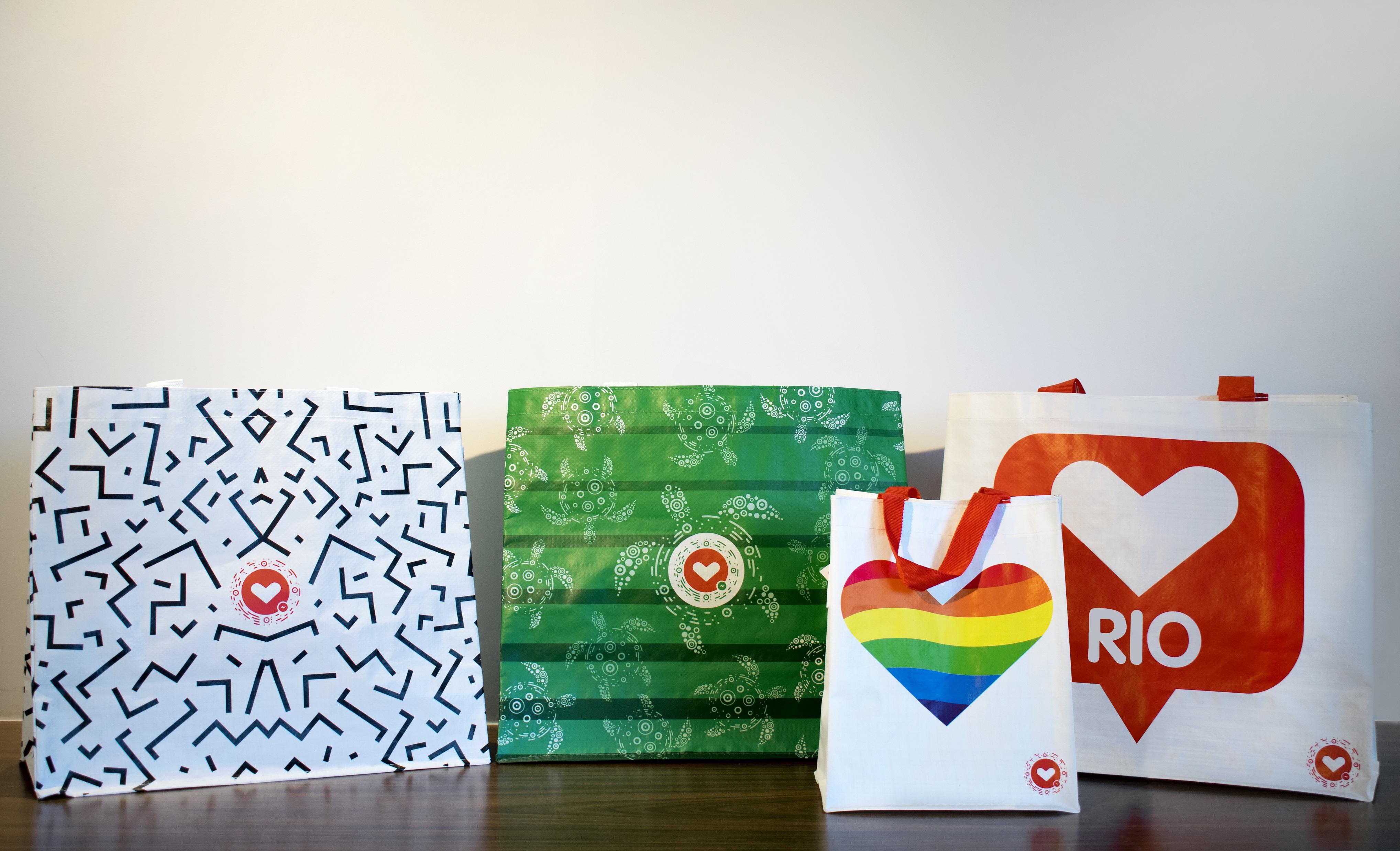 Na imagem há quatro bolsas. Da esquerda para a direita: bolsa branca com estampas de linhas pretas, bolsa verde com estampas de tartarugas, bolsa branca com um coração colorido com as cores do arco-íris e outra bolsa branca com um coração e o texto Rio