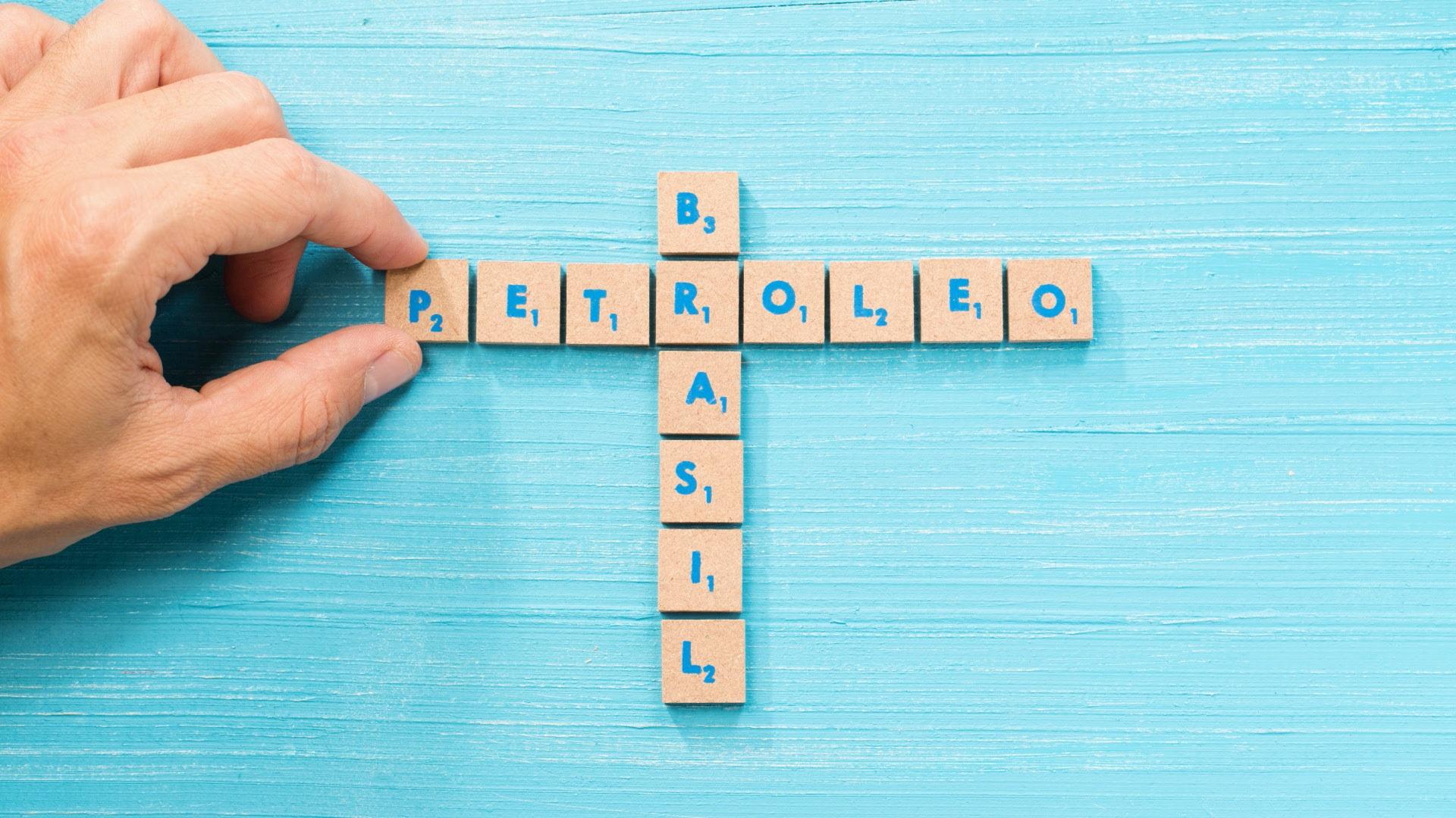 Na imagem, uma pessoa faz palavras-cruzadas em cima de uma mesa azul com bloquinhos contendo letras. Na horizontal, a palavra petróleo. Na vertical, a palavra Brasil. As duas palavras cruzam na letra R.