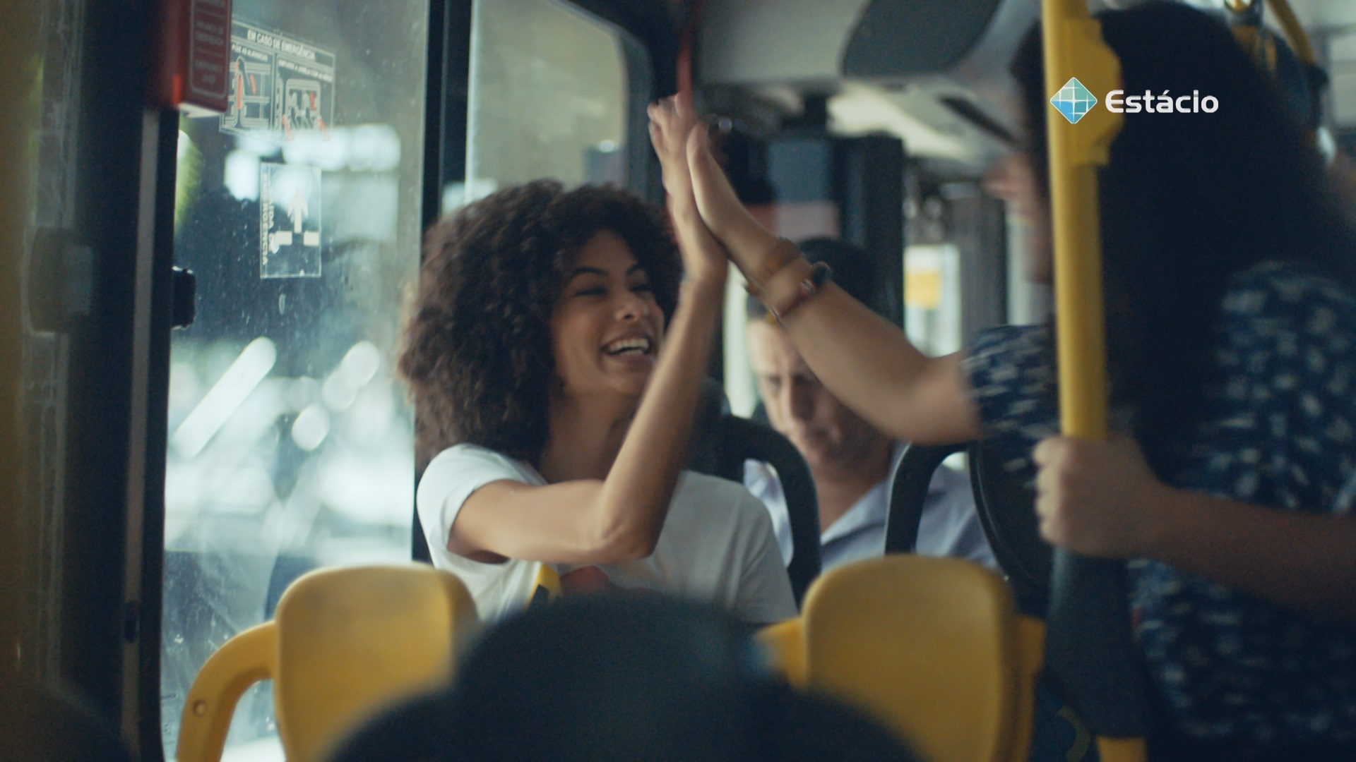 Dentro de um ônibus, duas estudantes se cumprimentam.