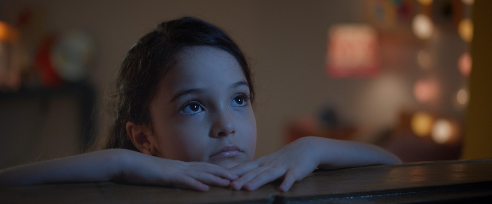 Uma menina apoiada em uma janela olha para o céu