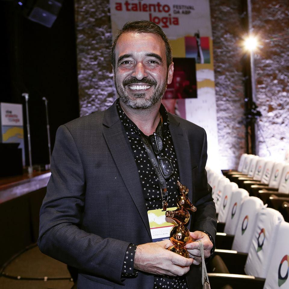 Márcio Borges segurando o prêmio da ABP.