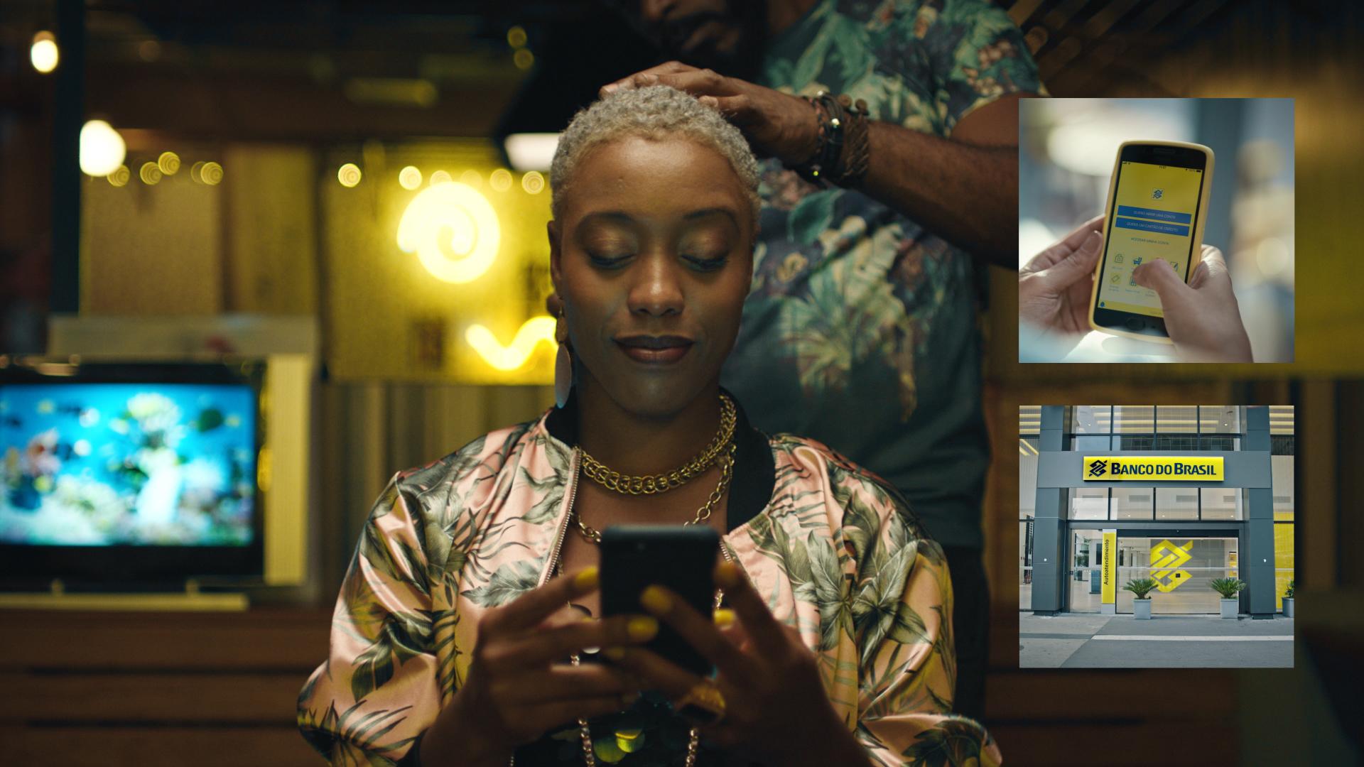 Uma mulher mexe no aplicativo do Banco do Brasil enquanto um cabeleireiro mexe em seu cabelo.