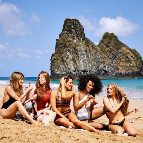 Na praia, Giovanna Ewbank e Luiza Sonza estão com outras três mulheres cuidando de seus cabelos.