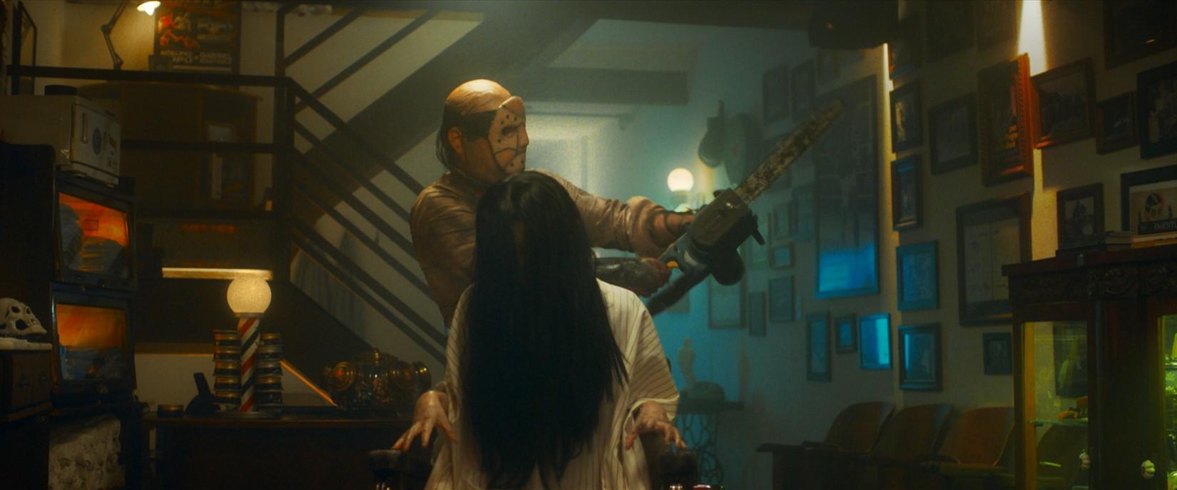 Dentro de uma casa, um rapaz com uma moto-serra e uma menina com o rosto coberto pelos cabelos