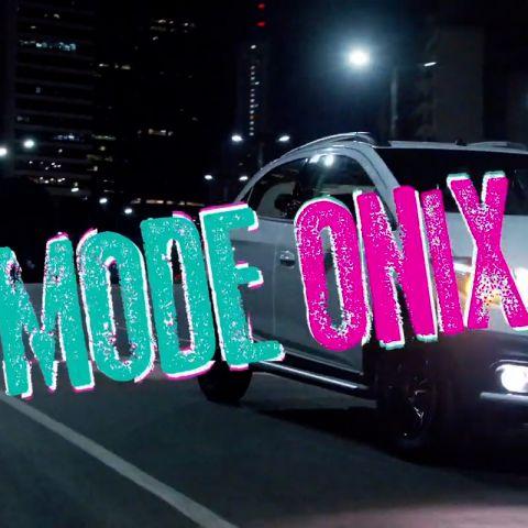 À noite, o Chevrolet Onix percorre uma rua. Há o logo Lollapalooza e o texto: Mode Onix