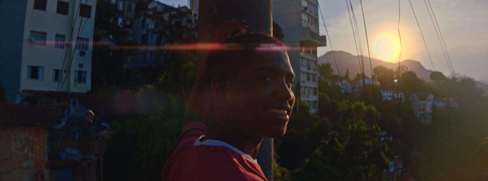 Um rapaz sorri em uma rua ao pôr-do-sol