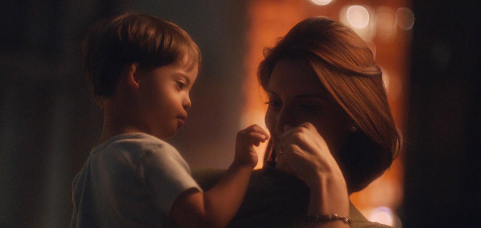 Uma mãe carregando seu filho e se cumprimentando.