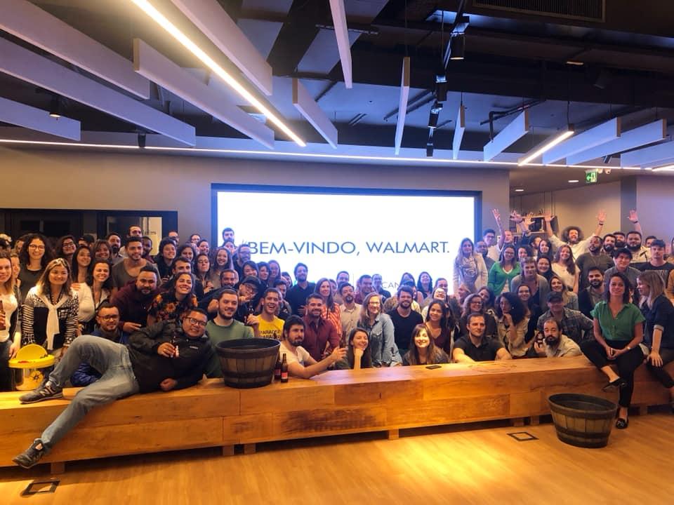 """Time da WMcCann São Paulo. No telão da recepção há o texto """"Bem-vindo, Walmart"""""""