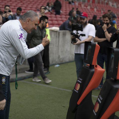 O técnico da seleção brasileira Tite cumprimenta os mascotes Mastercard.