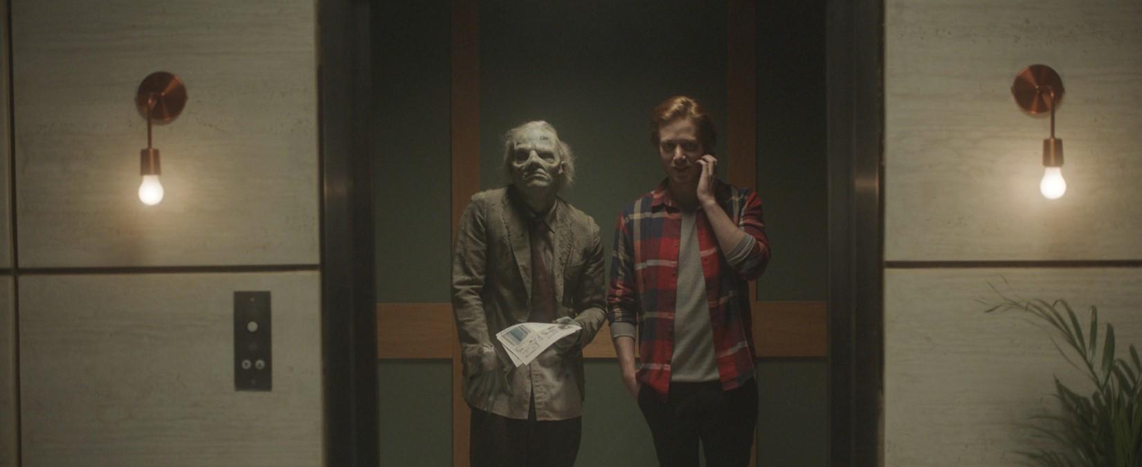 Dentro de um elevador, um homem conversa pelo celular, ao lado de um zumbi.