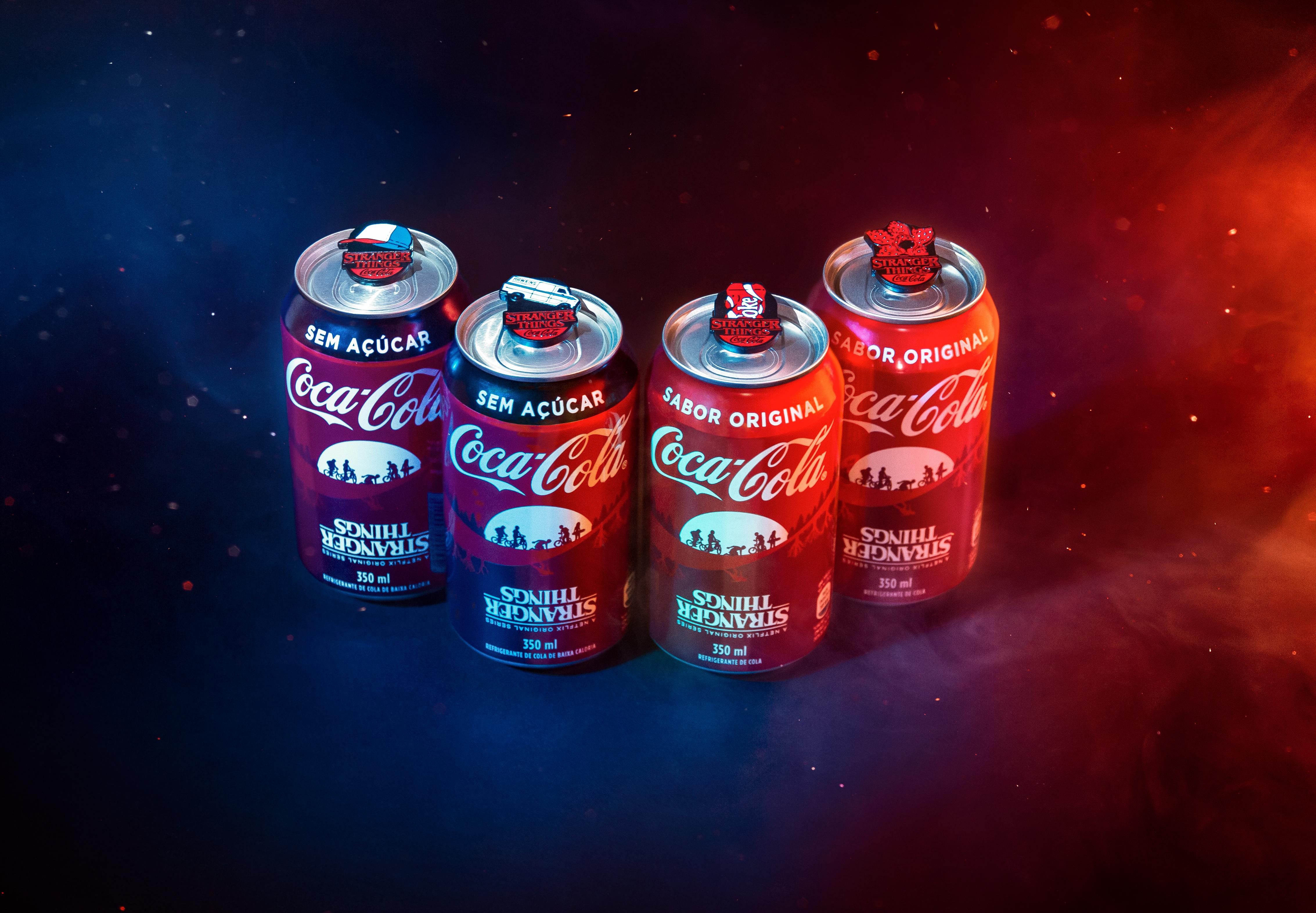 Quatro latas de Coca-Cola Pin Tabs edição Stranger Things, uma do lado da outra.