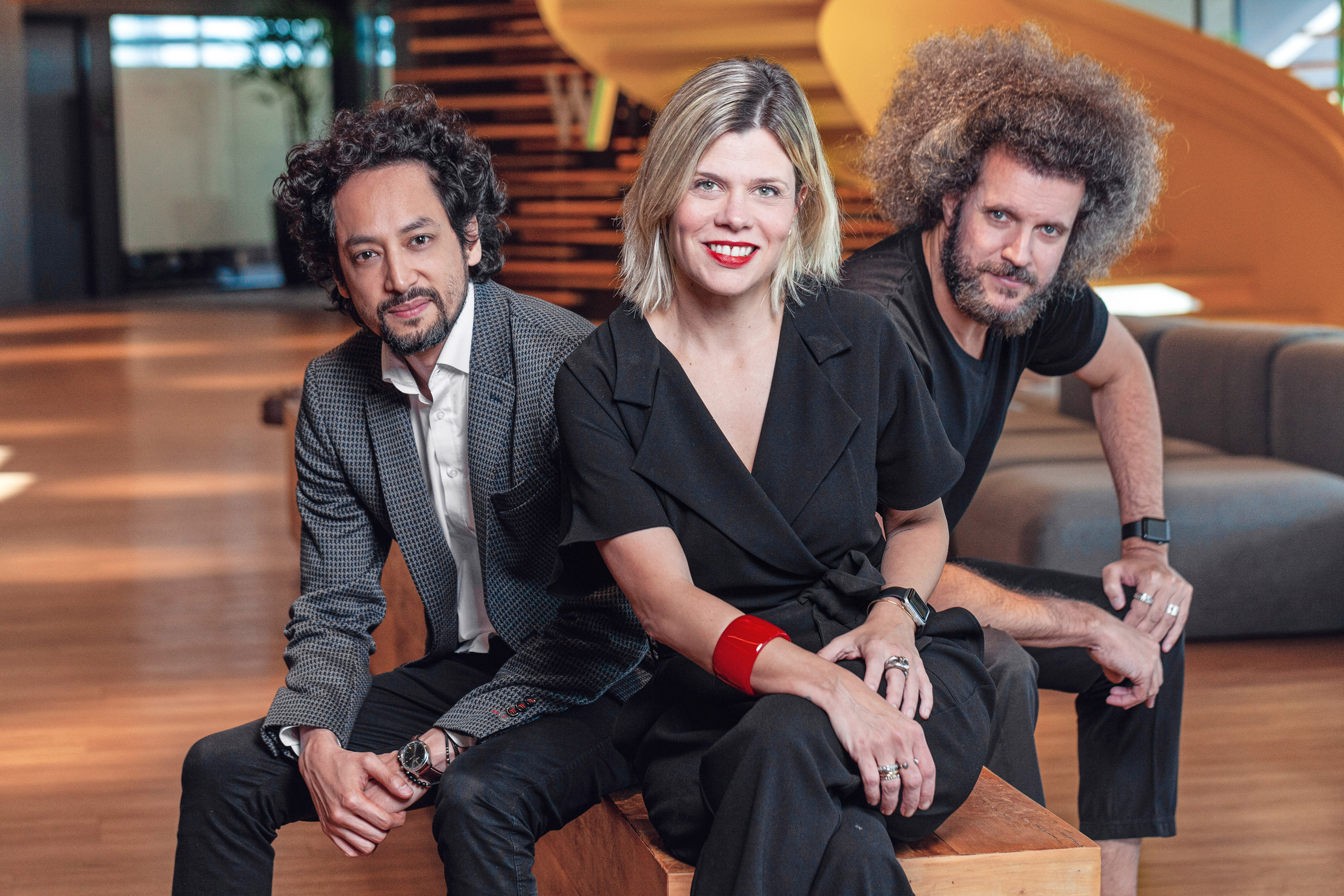 Kevin Zung, Renata Bokel e Hugo Rodrigues sentados juntos na recepção da WMcCann.
