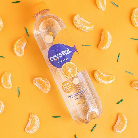 Garrafa de Crystal Sabores sobre um fundo na cor laranja e gomos de tangeria que simbolizam o sabor da água.