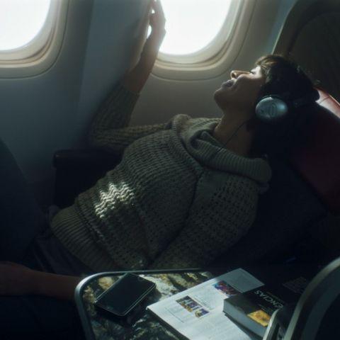 Mulher usando fone de ouvido sentada em cadeira de avião durante um voo.
