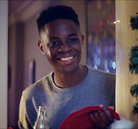 Dentro de casa, um jovem sorri olhando para o lado de fora da janela, enquanto segura uma garrafa de Coca Cola