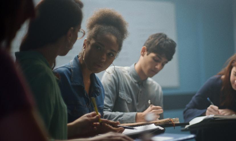 Três estudantes conversam e fazem anotações em seus cadernos