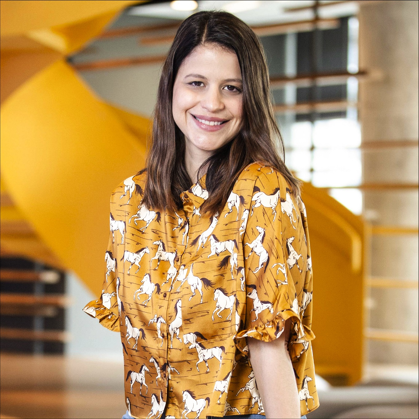 Foto da diretora de atendimento Joana Campanelli sentada na recepção da WMcCann