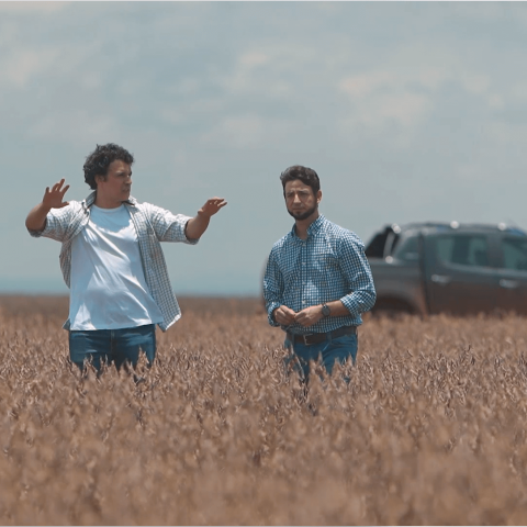 Dois homens conversam ao ar livre e no fundo uma Chevrolet S10.