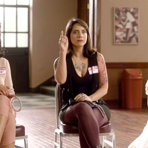 Três mulheres sentadas, uma ao lado da outra. A que está no meio, mantém a mão levantada, como se pedisse permissão para falar algo no grupo de apoio.