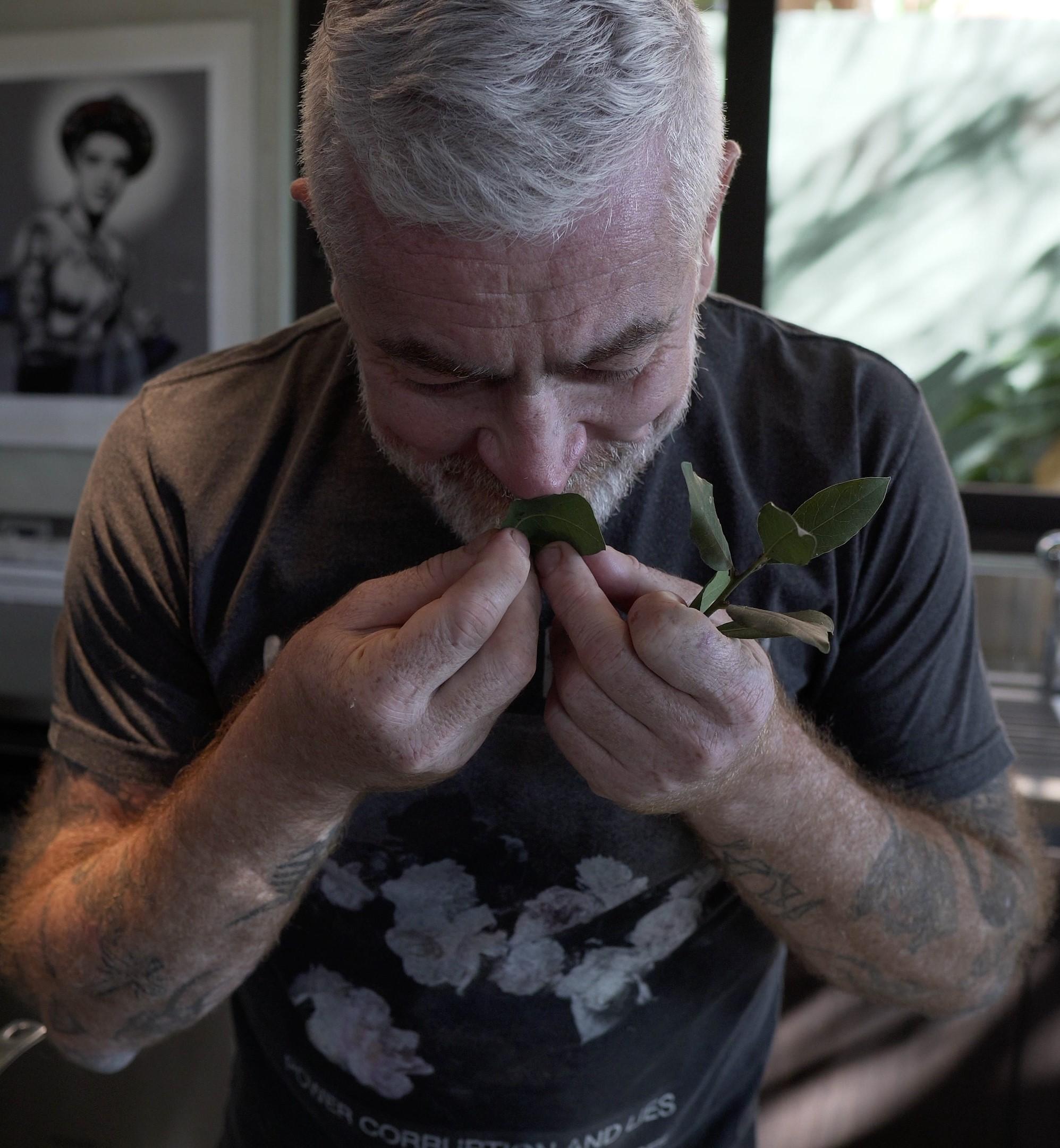 Chef Alex Atala cheira folhas de louro na cozinha de sua casa. Pequena