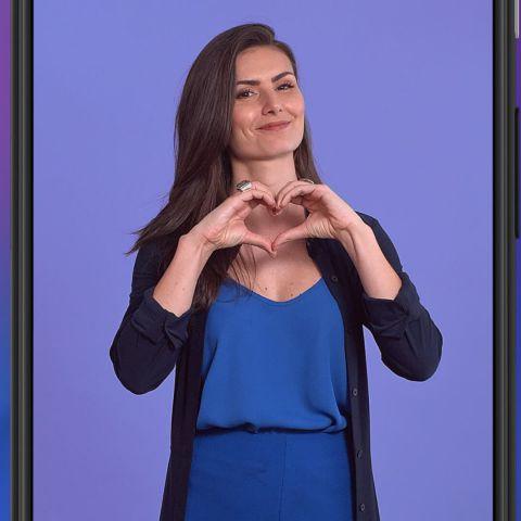 Foto da especialista em finanças, Nathalia Arcuri, fazendo o formato de um coração com as mãos, e o logo da Estácio no canto superior direito, tudo em fundo de cor azul.