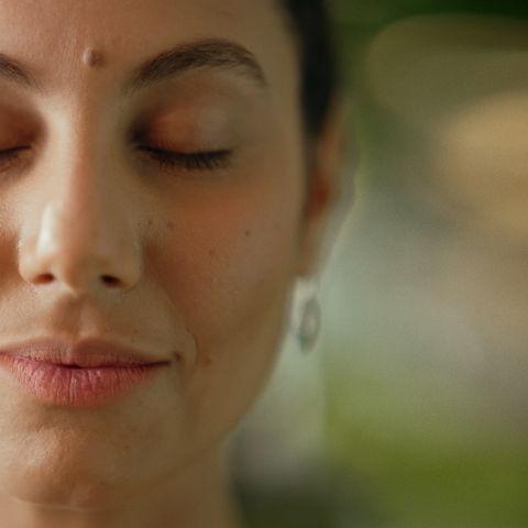 Imagem com foco no rosto de uma mulher que parece mentalizar sobre algo.