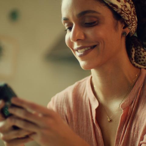 Foto de uma mulher com leve sorriso enquanto usa o celular