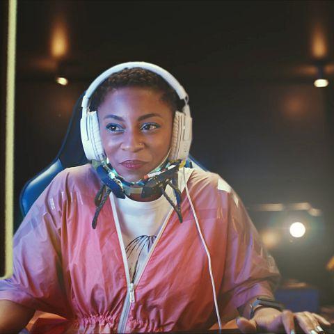 Na imagem, uma moça aparece sorrindo enquanto parece jogar online.