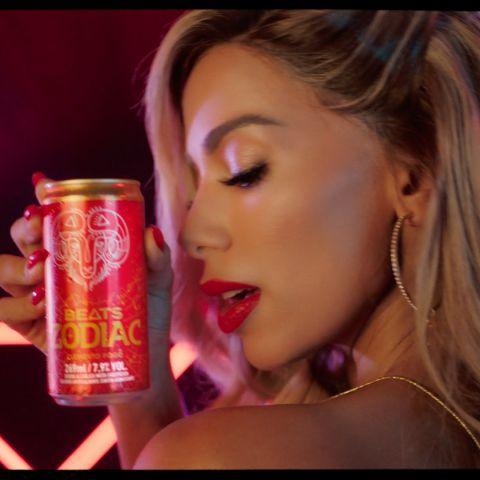 A cantora Aniita aparece de perfil segurando uma lata de Beats Zodiac do signo de Áries.