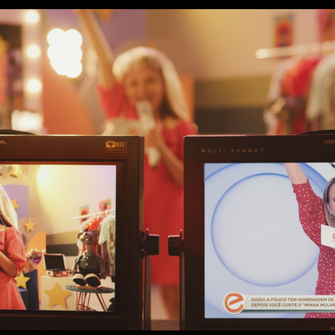 Na imagem, aparece numa tela a apresentadora Eliana, e ao fundo, uma garota que faz seu papel como apresentadora mirim.