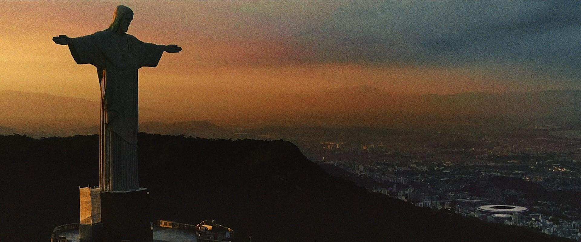 Na imagem, aparece a estátua do Cristo Redentor, e ao fundo o estádio do Maracanã.