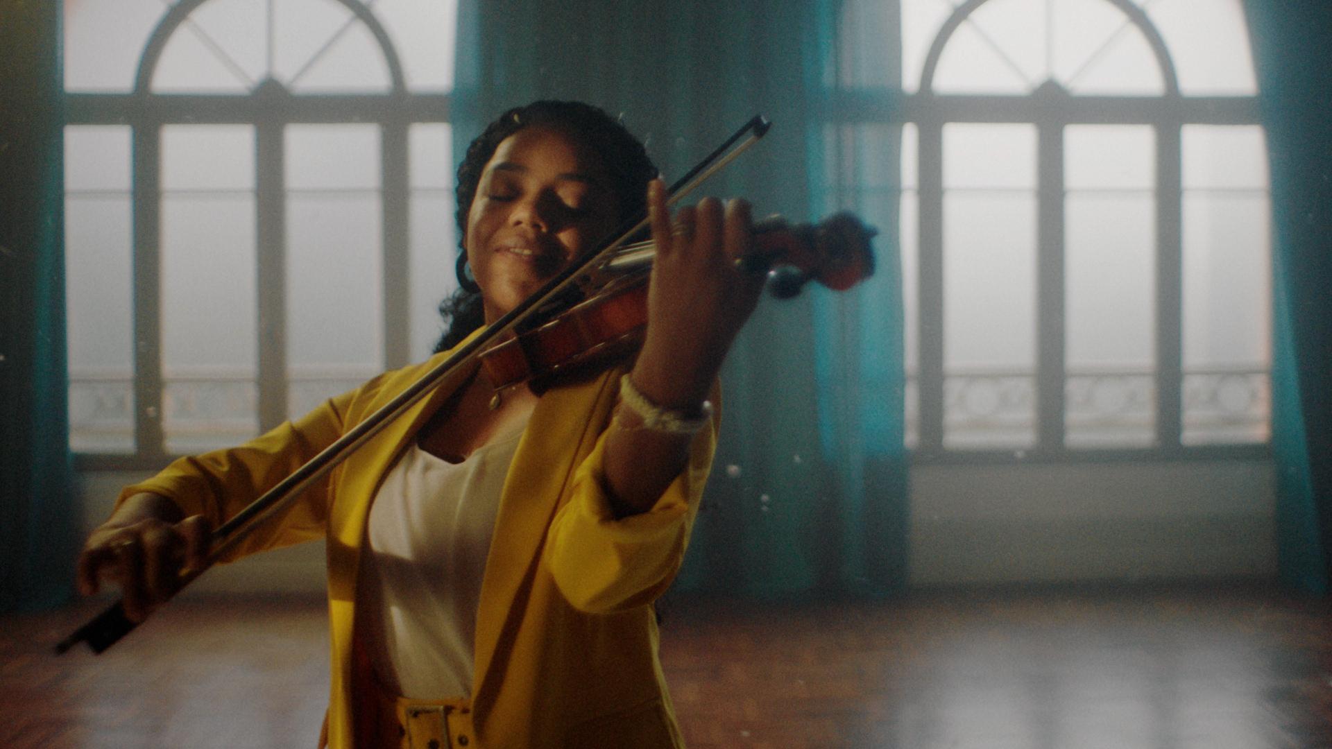 Na imagem, uma mulher vestida de blusa amarela toca violino com leve sorriso no rosto.